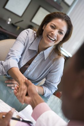 Woman shaking doctor's hand at IVF clinic